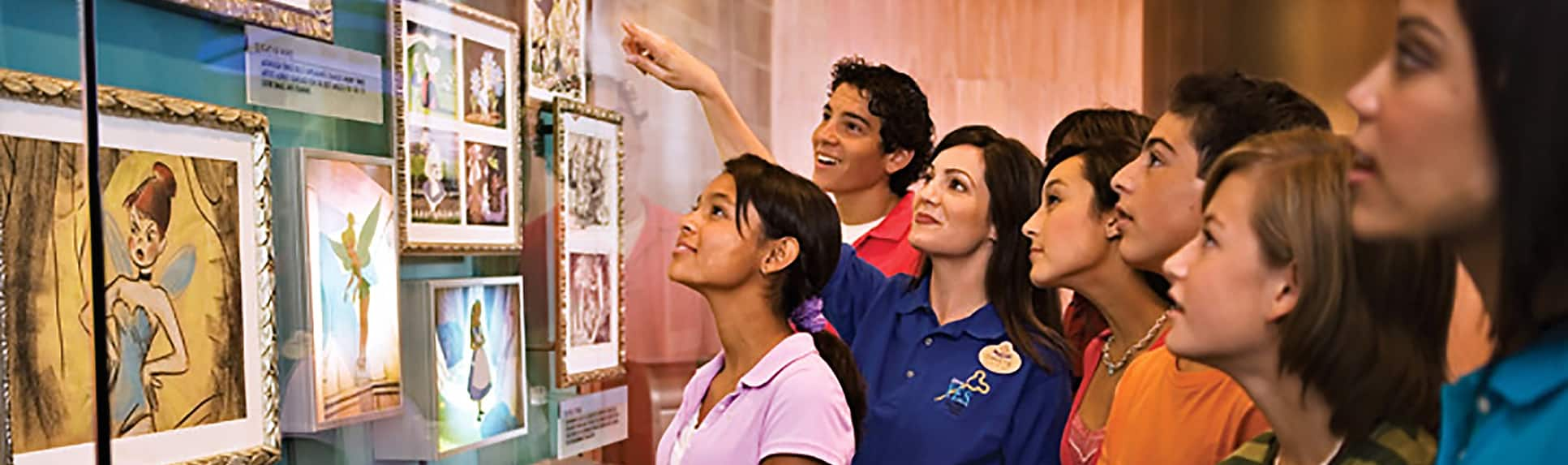 A Cast Member showing young adults Disney portraits encased in a glass display