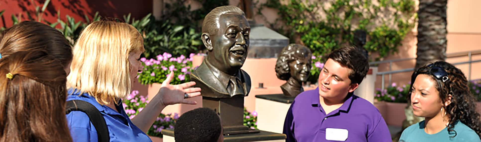 Children watching a Cast Member gesturing towards a bust of Walt Disney