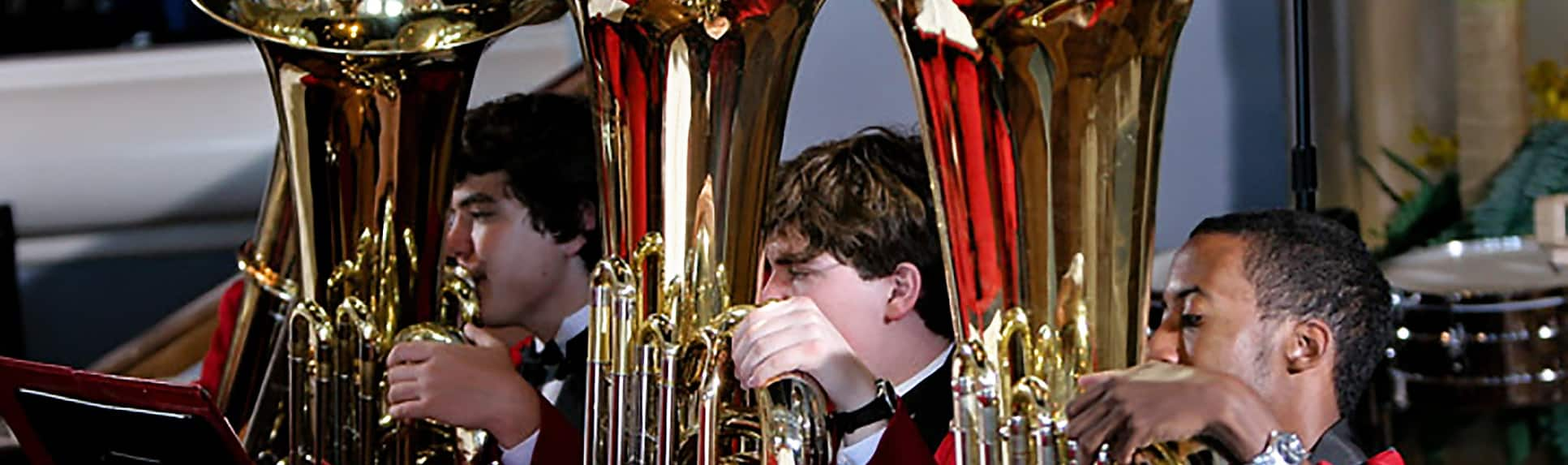 Young adults holding brass instruments and reading sheet music