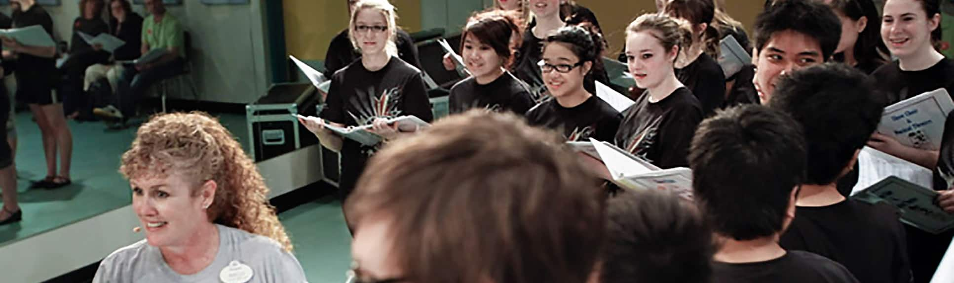 A Cast Member facing young adults holding binders