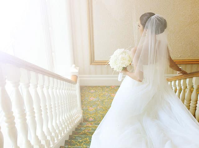 A bride dressed in a wedding gown and veil, walking down a staircase