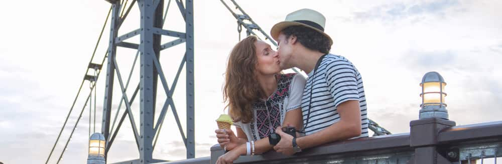 A man and woman kiss while standing on a bridge