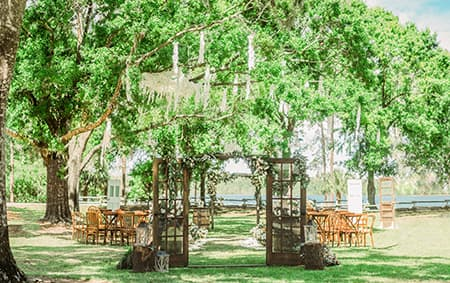 A canopy of trees provide shade over seating for an outdoor wedding