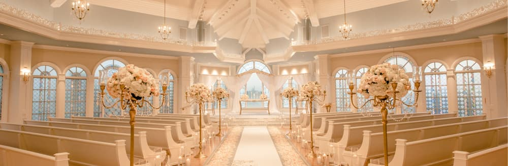 Sunlight Shines Through The Arched Stained Glass Windows Of A Wedding Chapel With Chandeliers And