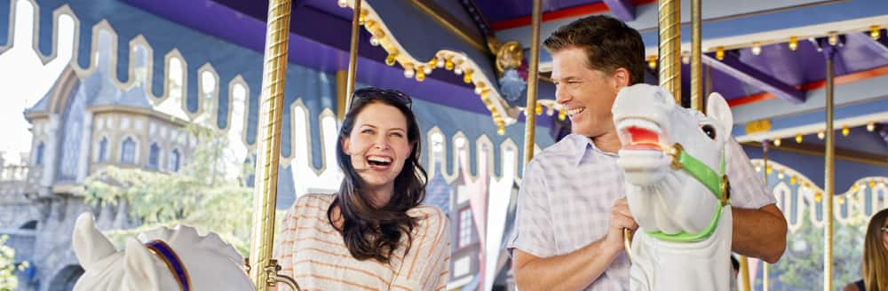 A woman and a man smile widely as they sit atop wooden horses on an old fashioned carousel ride