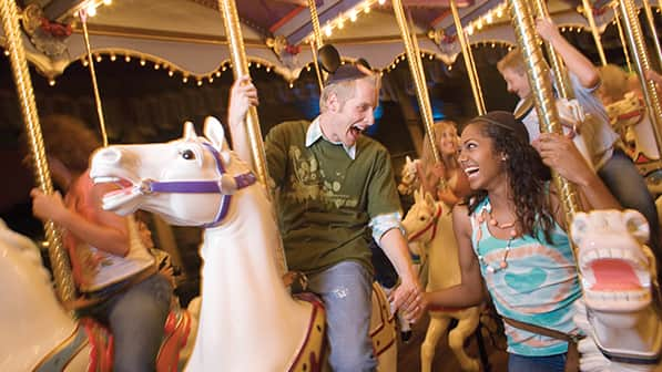 Young adults wearing Mickey ears and holding hands on a carousel