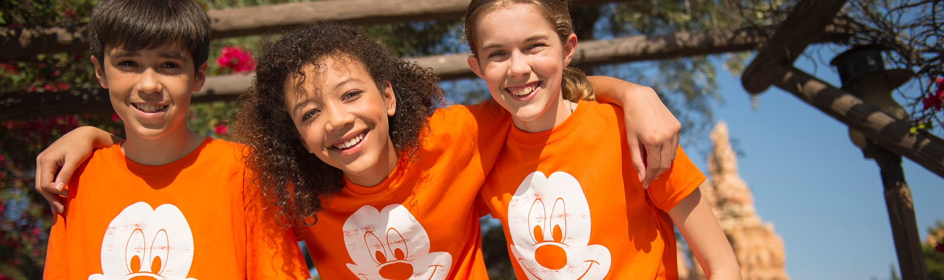 Smiling kids wearing matching shirts with Mickey Mouse logos