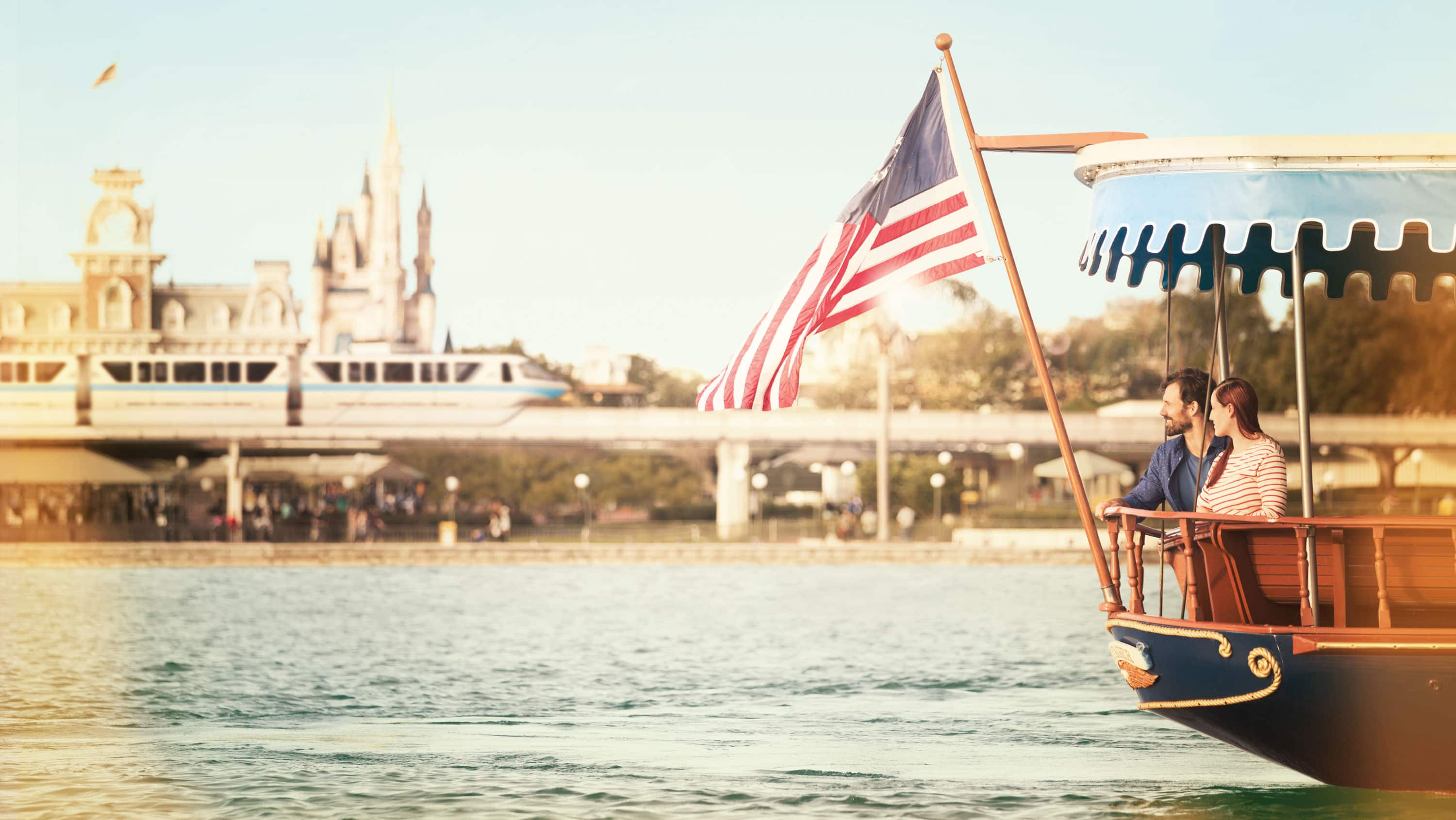 A couple glides past Magic Kingdom park aboard an American flag bearing ferryboat.