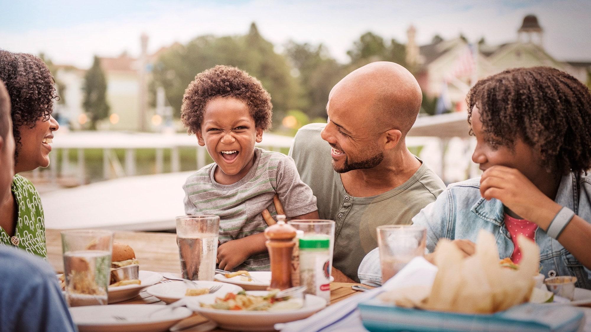 屋外のダイニングテーブルで食事をする 5 人連れの家族