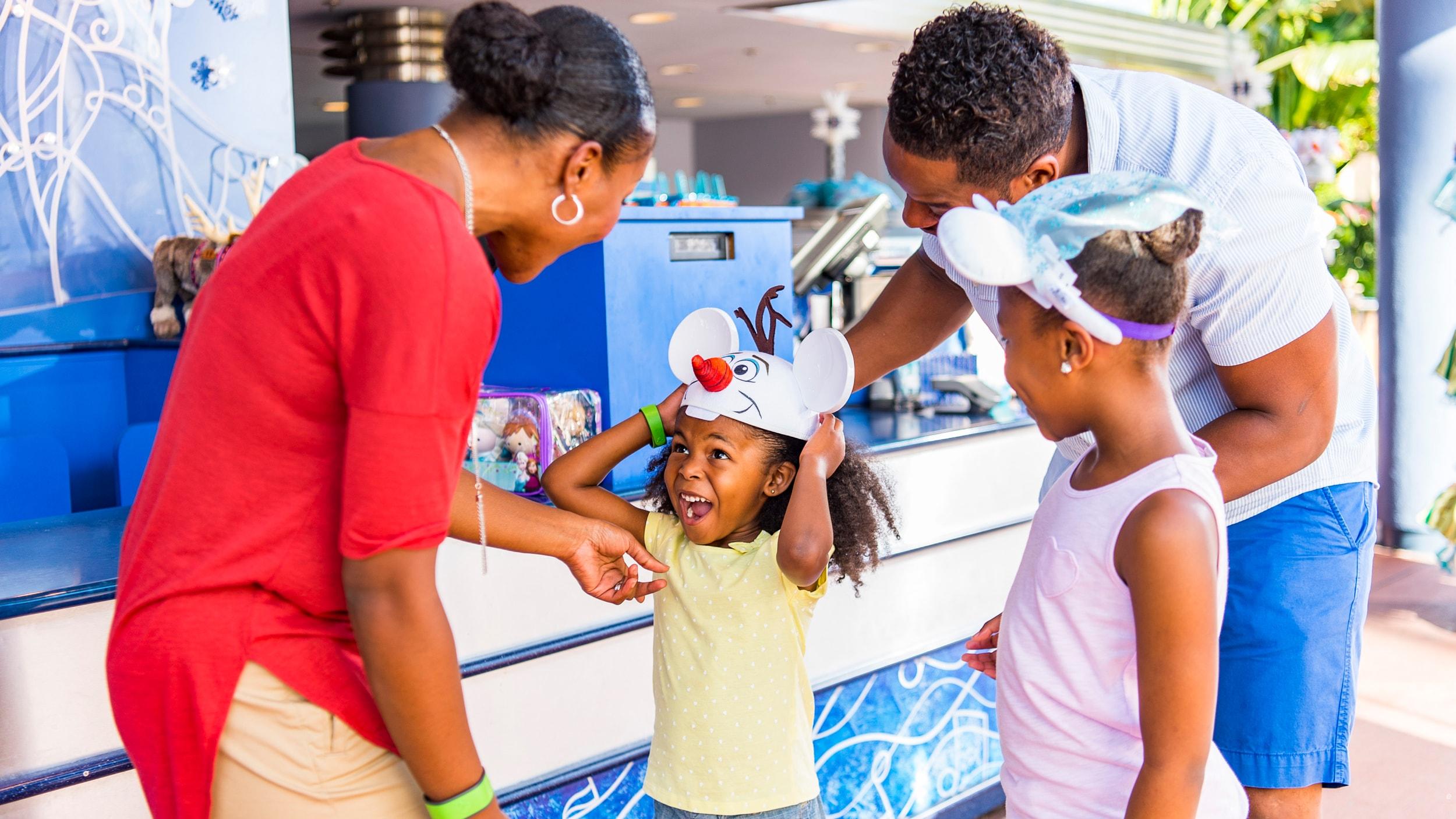 テーマパークの屋外でほほ笑み合う父母と 2 人の女の子