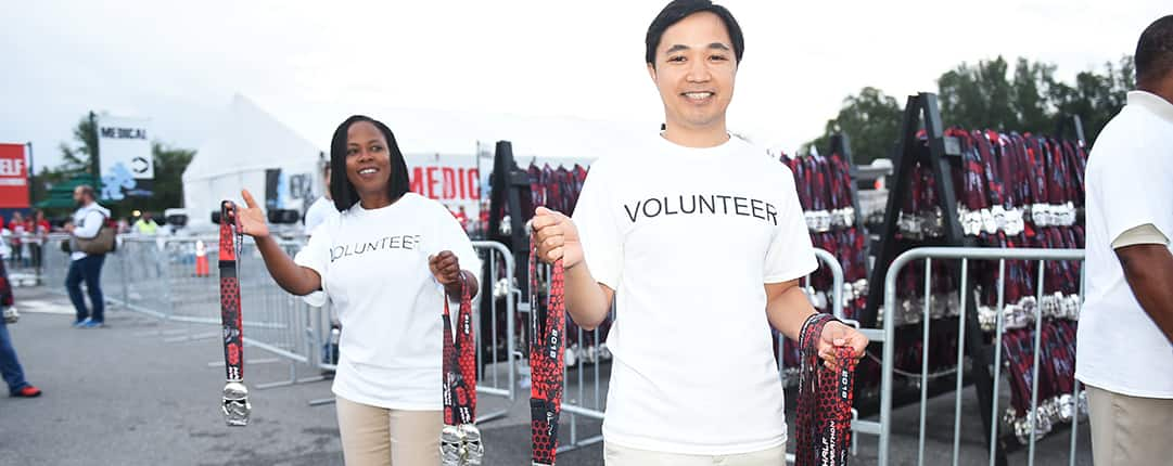 Volunteers stand along the race route ready to pass out Star Wars lanyards to runners